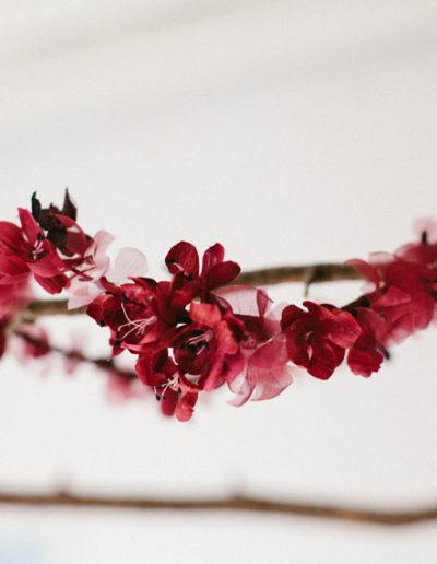 Corona de flores de seda burdeos.