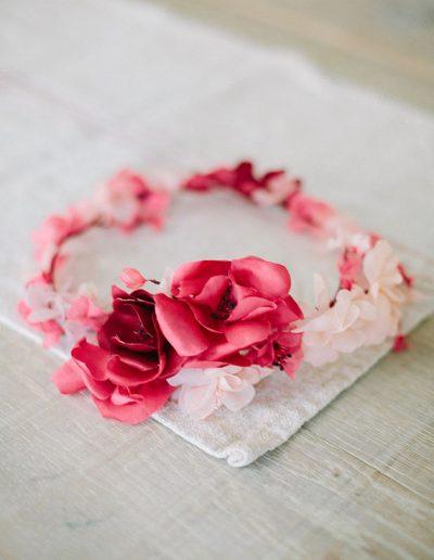 Corona de flores de seda rosa y roja.